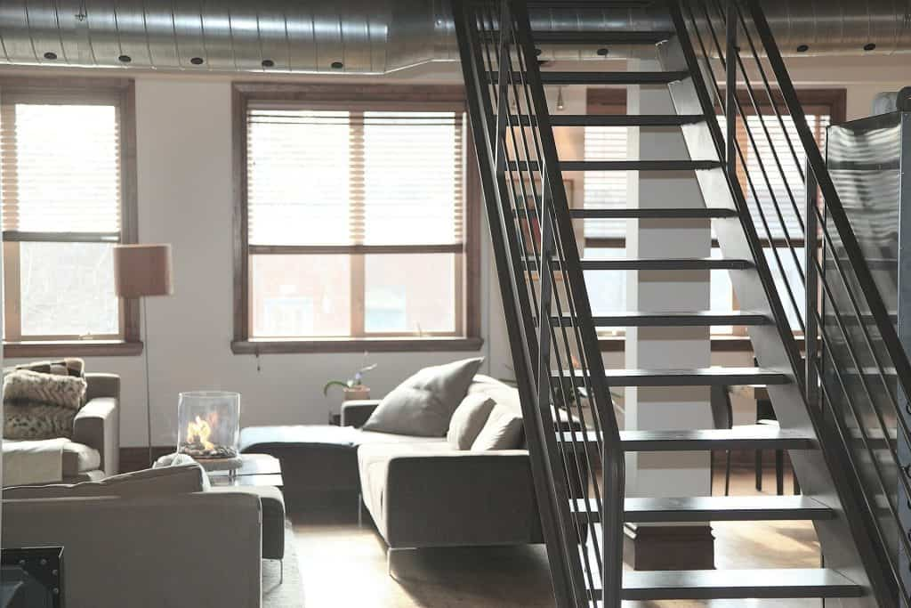 Industrial Popular Interior Design Style and the Home Decor pieces to have for each of them: Living room with large pipe in the ceiling and metal stairs