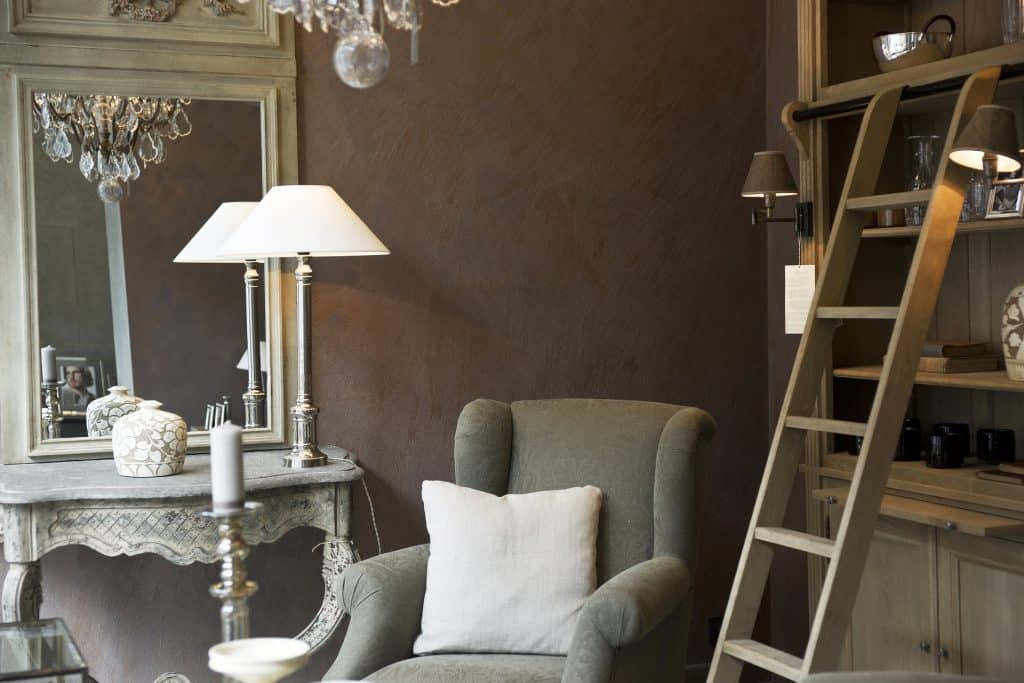 French Country Popular Interior Design Style and the Home Decor pieces to have for each of them: Cosy armchair and antique mirror on antique desk aside a wooden bookshelf and shelf