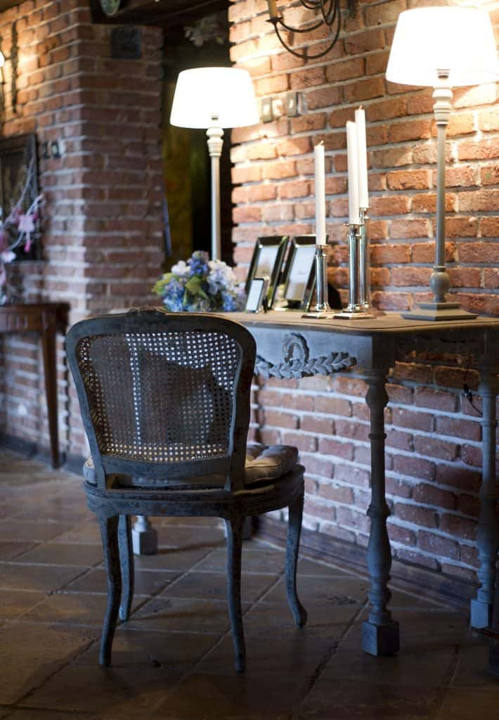 French Country Popular Interior Design Style and the Home Decor pieces to have for each of them: Antique desk and chair with chandeliers and hight lamps in front of brick wall