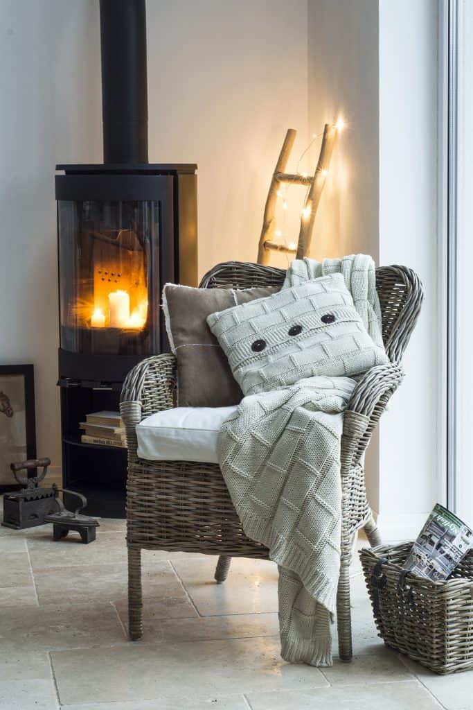 Farmhouse Popular Interior Design Style and the Home Decor pieces to have for each of them: Waived armchair with throw and cushions in front of fireplace
