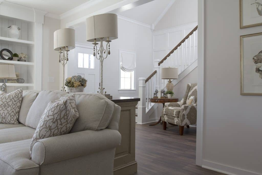 French Country Popular Interior Design Style and the Home Decor pieces to have for each of them: Cosy living room with neutral colour palette with an armchair and   large base lamps